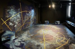 An empty stage decorated with celestial objects including constellations and planets