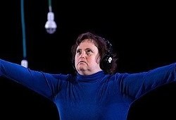 A dancer stands with their arms wide open in a black background, with lightbulbs hanging down from the sky