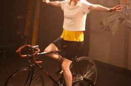 AN actor sit on a bicycle with their arms outstretched