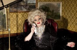 Myra Dubois sits in an armchair, dabbing at her face with a handkerchief