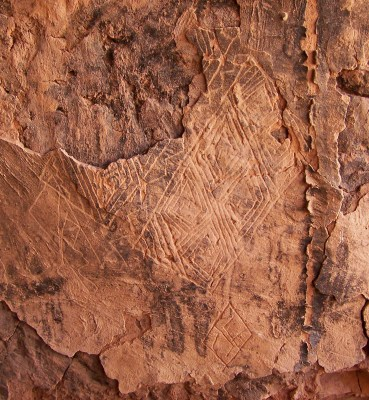 Building mural from the Cedar Mesa area showing the image of at least one ornately woven twined yucca sandal and other woven textile design elements incised into the interior plaster of a kiva dating to the early thirteenth century.