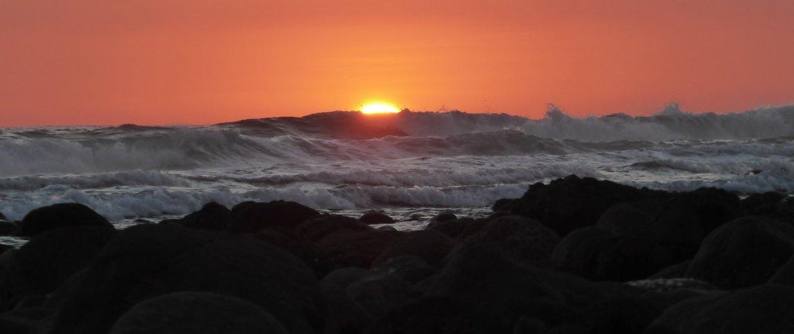 De zon wordt opgegeten door de golven in El Zonte.
