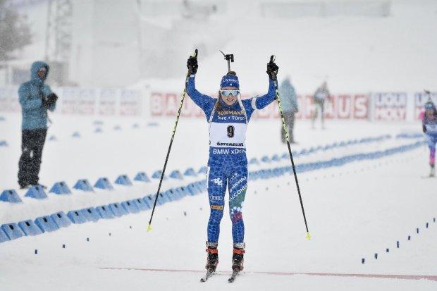 Dorothea Wierer, braccia alzate all'arrivo, festeggia la vittoria nella gara di partenza in linea: l'azzurra è la prima biatleta Italiana nella storia a vincere un oro ai Mondiali