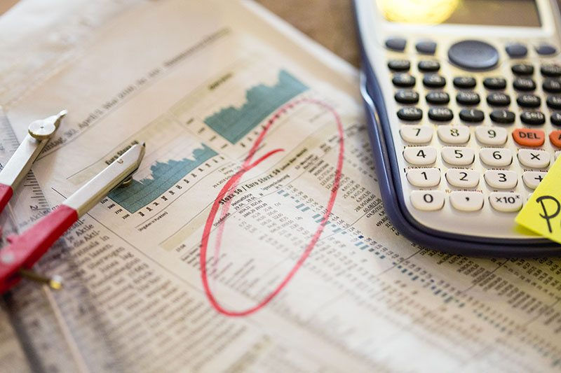 Taschenrechner liegt auf einer Zeitung mit Aktienkurse.
