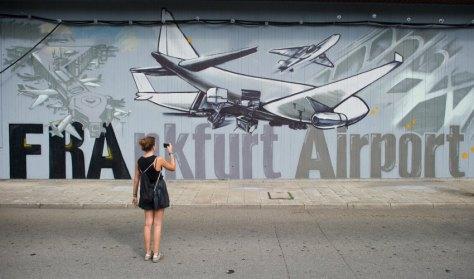 """Eine junge Frau fotografiert am 14.08.2015 am Busbahnhof vom Flughafen in Frankfurt am Main (Hessen) mit ihrem Smartphone einen Teil einer 360 Meter langen Mauer, die mit Graffiti-Spraykunst von Künstler Helge """"Bomber"""" Steinmann verziert worden ist. Um den Busbahnhof aufzuwerten und den dort wartenden Reisenden ein besonderes visuelles Erlebnis zu bieten, wurde die Mauer im Graffiti-Stil verschönert. Foto: Christoph Schmidt/dpa +++(c) dpa - Bildfunk+++"""