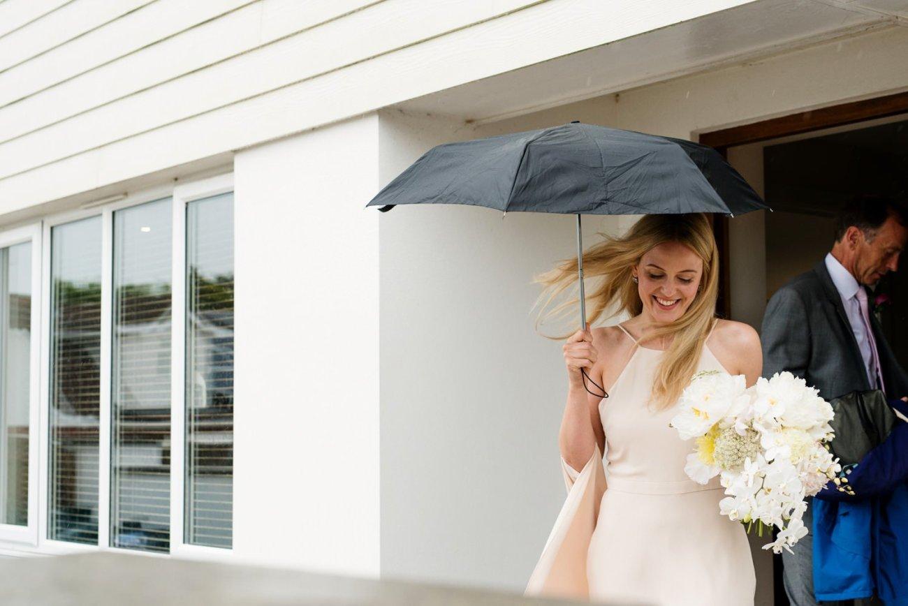 Smiling in the rain at Tunnels Beaches Wedding Photographer Devon
