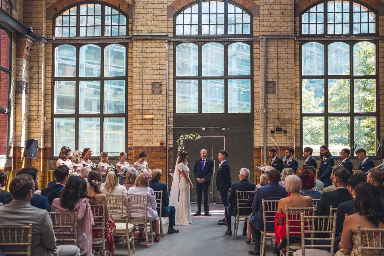 Wedding guests watching a warehouse wedding ceremony in London with lots of string lights