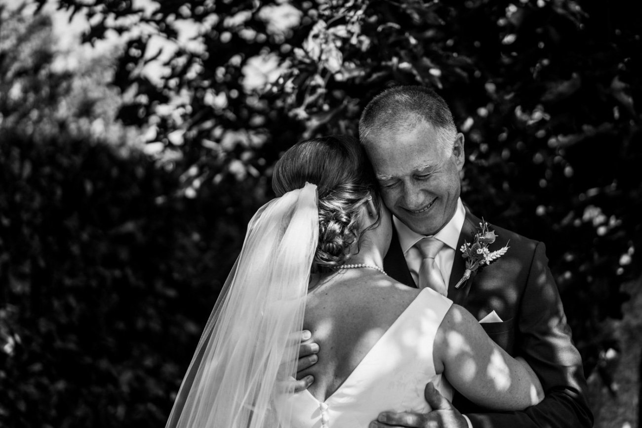 Black and white image of bride and dad hugging at a Birmingham wedding