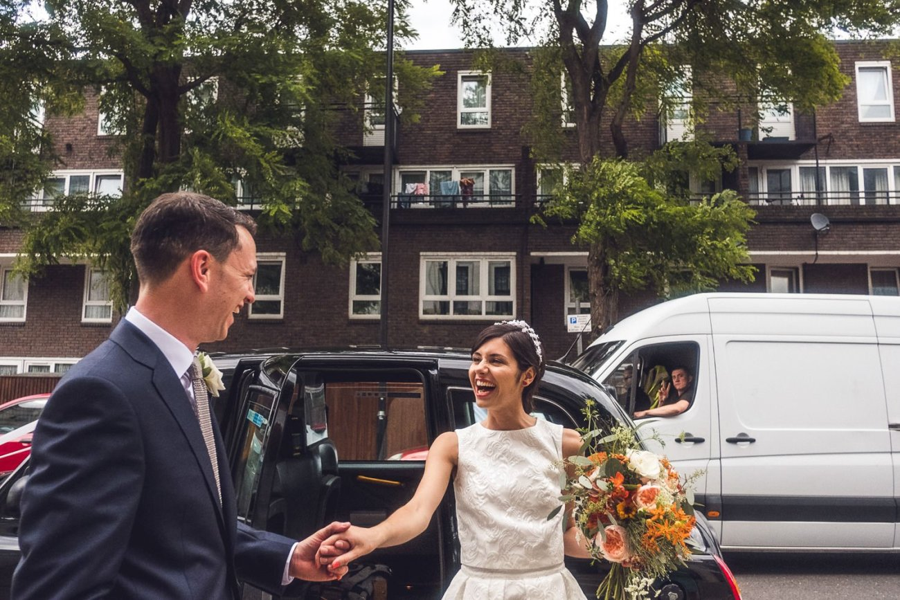 Laughing bride getting out of a taxi in East London with white van men watching