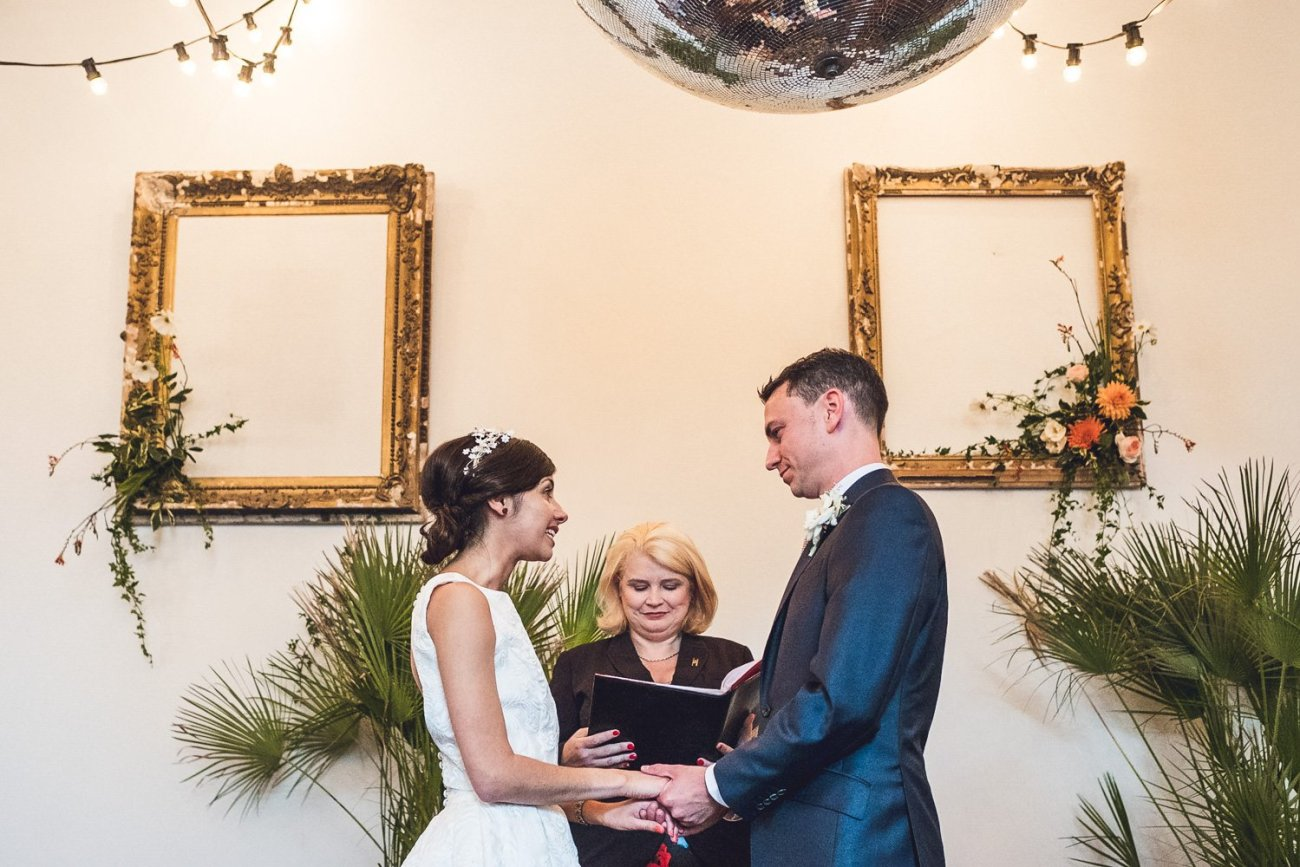 Couple in front of ceremony backdrop at humanist wedding