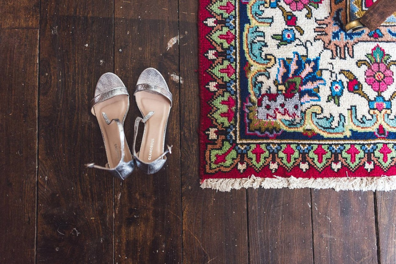 Silver shoes next to antique rug at homme house