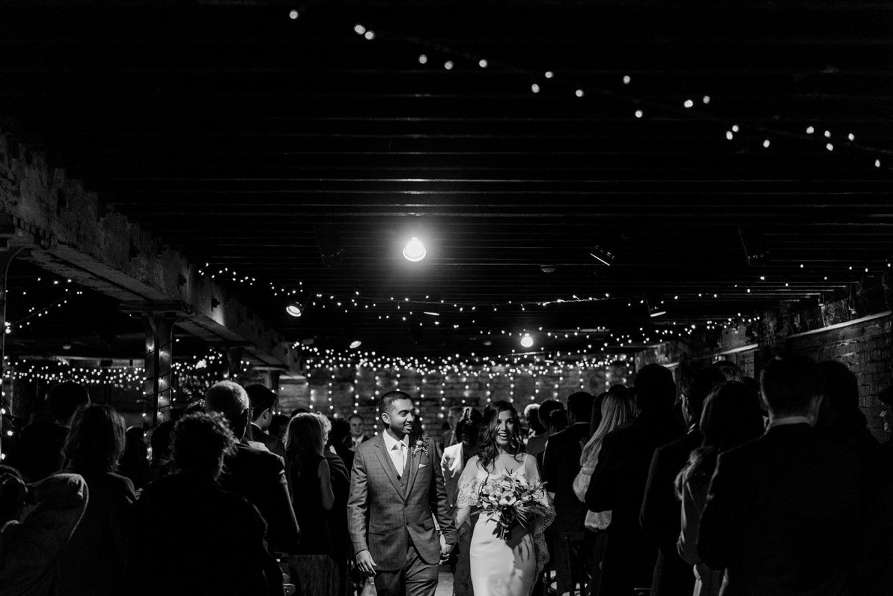 Black and white bride and groom exit trinity buoy wharf