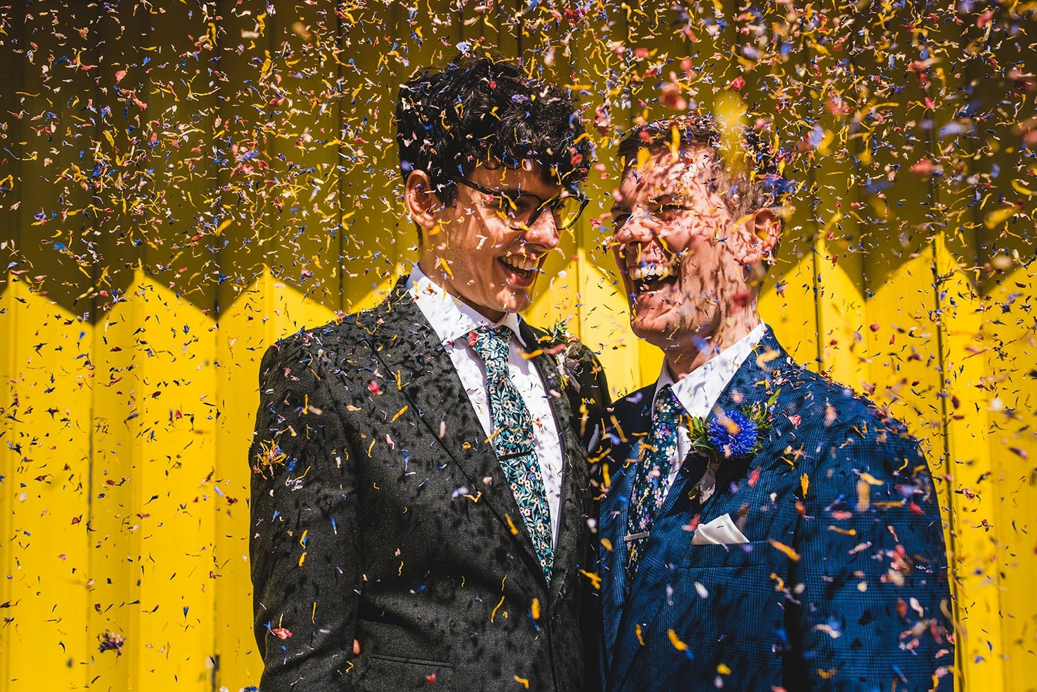Gay couple laughing in shower of confetti