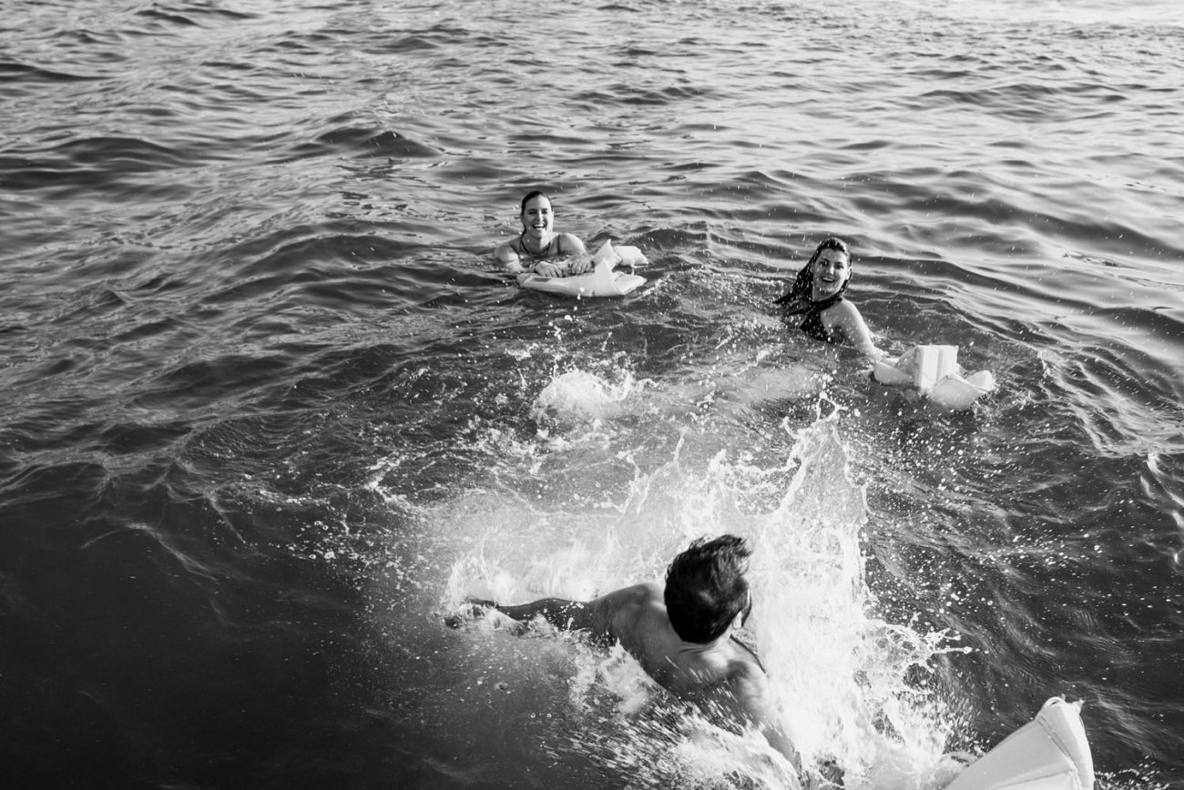 Black and white image of people diving into water Dubai
