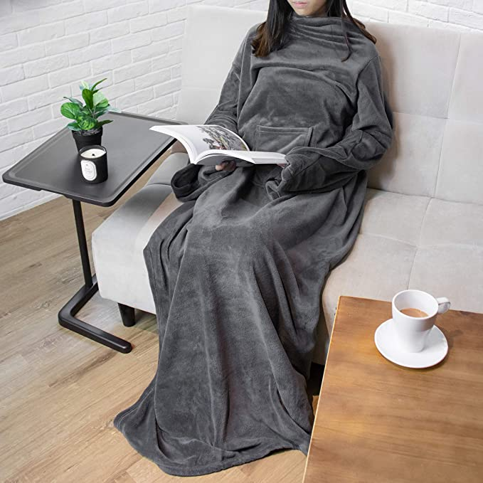 Woman sitting on a couch reading a book while wearing a wearable blanket with sleeves.