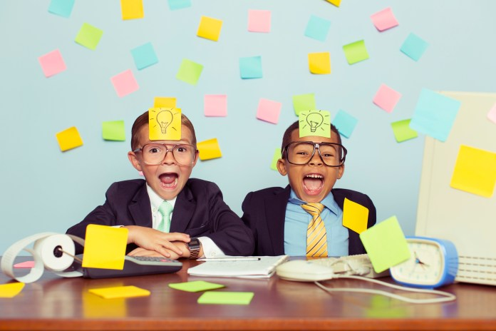 Two young businessmen sit at their office computer desk with ecstatic expressions on their faces and light bulb sticky notes on their foreheads.  They are excited as they have thought of new business ideas.  They are wearing a suit and tie and glasses.