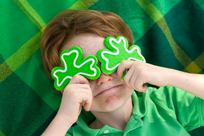 Redhead and freckle face Irish boy leprechaun with shamrock cookies over his eyes.
