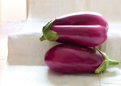 Two purple eggplants on white cloth on table
