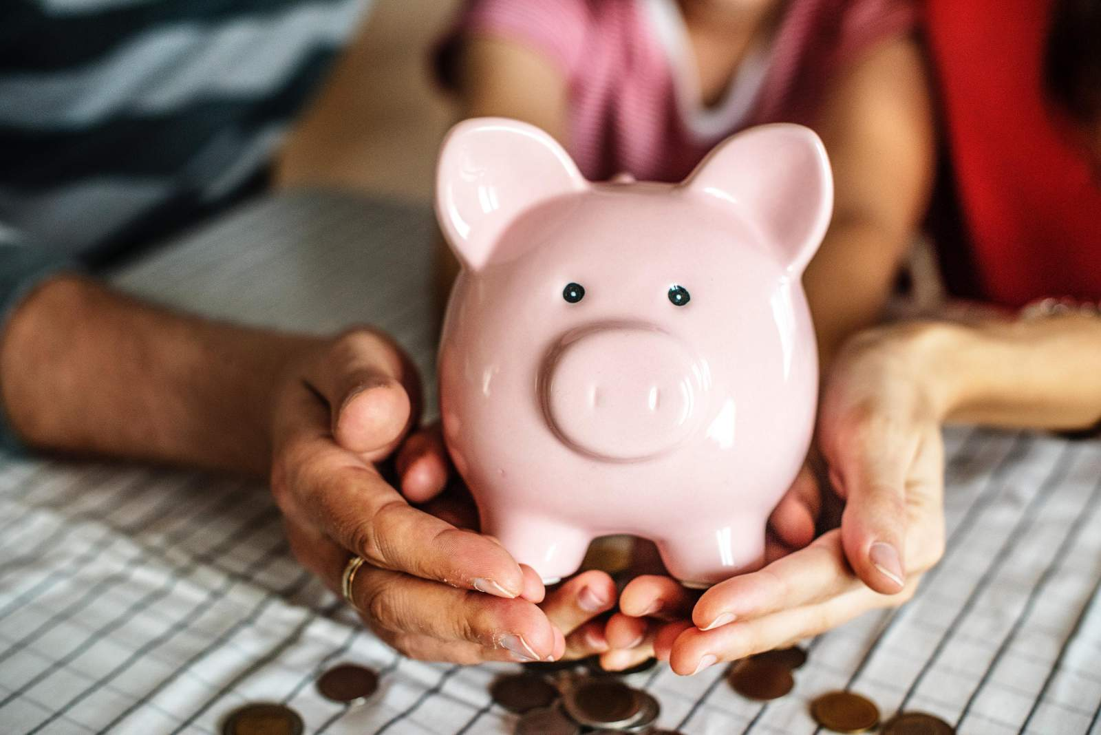 hands holding a piggy bank with coins around