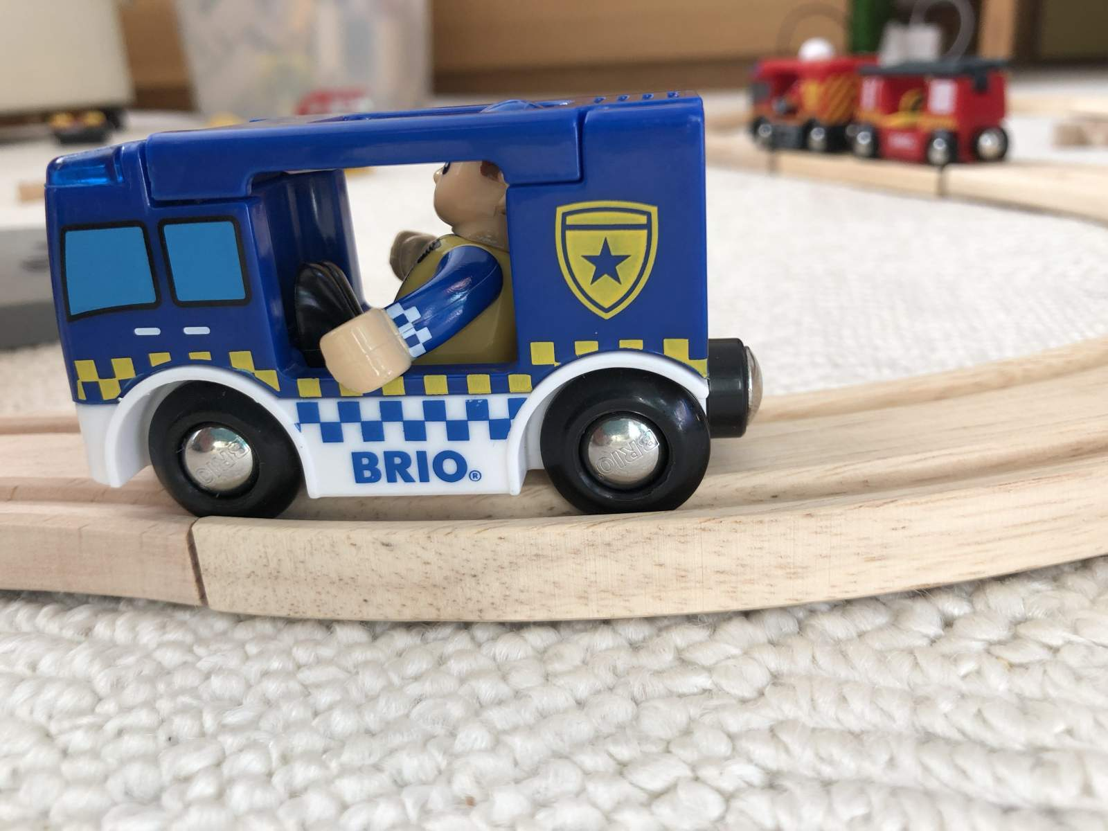 Brio police car on wooden track with fire engine train in background