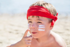 Who am I? Sunscreen (suntan lotion) is on hipster boy face before tanning during summer holiday on beach. Caucasian child (kid) is smiling in sunny day (not far from Trieste, Italy). Copy space.