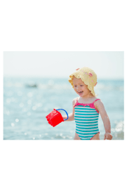 sun safety baby at the beach in a sun hat with sand bucket
