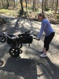 woman pushing down on a jogging stroller handles