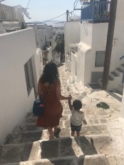 Mom and toddler walking down steps in Mykonos, Greece.