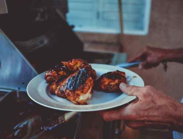 Gegrillte Hähnchen werden auf einen Teller gelegt. Im Hintergrund ein Grill.