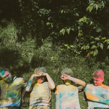 The Crookes band lying on grass covered in paint