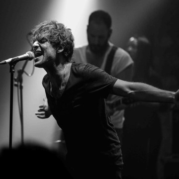 Black and white image of Paolo Nutini singing on stage