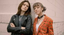 Promo photo of Larkin Poe standing in front of brick wall for 'Holy Ghost Fire' video
