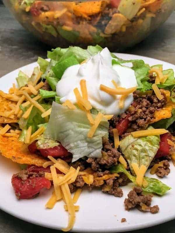 Easy Dorito Taco Salad Recipe is a cinch to make. It features spicy taco flavors that will please a crowd. Easy Dorito Taco Salad is perfect for a family supper, a tailgating party, football games, or any holiday. #dorito #taco #salad #supper #dinner