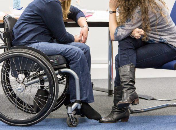Duas mulheres falam por uma mesa.  Um deles é um usuário de cadeira de rodas.