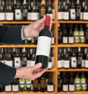 Sommelier offering bottle of red wine to customer