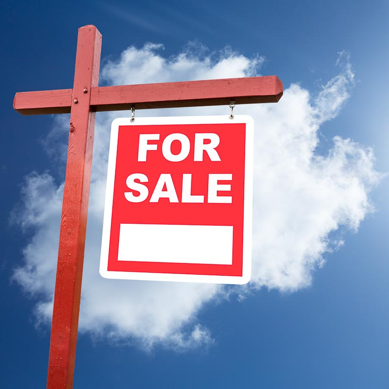 Realtor installed for sale sign for house or real estate set against blue sky and clouds
