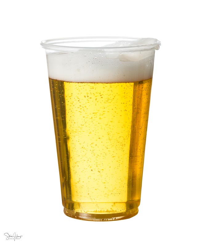 Plastic glass of beer isolated against white background