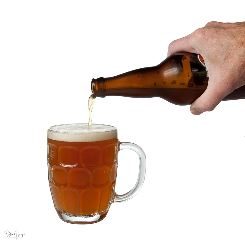 Mans hand pouring a pint of beer from a bottle isolated against white background