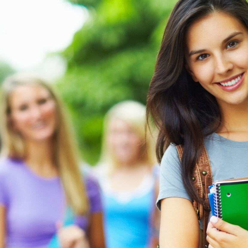 Beautiful, young woman standing in the campus and smiling