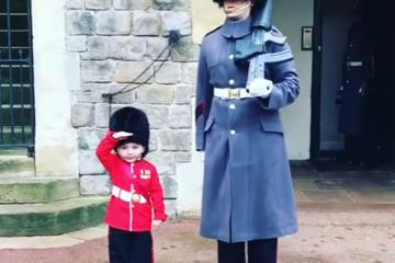 A queen's guardman poses with toddler who's dressed as a little guardsman.