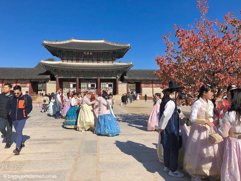 Conexão Coréia do Sul - Gyeongbokgung Palace, cheio de pessoas vestidas com roupas tradicionais, o  hanbok.