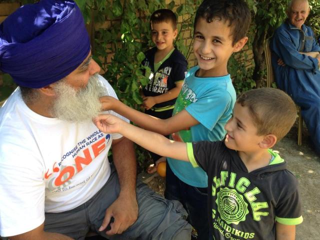 """The Sikh beard brining smiles to the Assyrian refugee children in Erbil, Iraq !  Ravinder Singh,CEO of Khalsa Aid ( UK ) has been organising the relief program for the refugees in Iraq.  The refugee children have become accustomed to having this turbaned/bearded guy around and always show him so much love. They call him """"Amo"""", uncle"""
