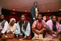Cette photo montre une scène de « Henry Box Brown ». La comédie musicale s'inspire du riche héritage des negro spirituals du 19e siècle, nés de la souffrance et des difficultés endurées par les peuples esclaves d'ascendance africaine. Ces œuvres transmettent souvent des valeurs et des idées spirituelles profondes. « Toutes ces chansons sont issues de l'oppression, du pardon accordé aux oppresseurs, des chansons qui vous distrayaient de la brutalité de la vie dans laquelle vous étiez plongés, explique le directeur musical et co-compositeur du spectacle. Toutes ces chansons sont connectées à Dieu... »