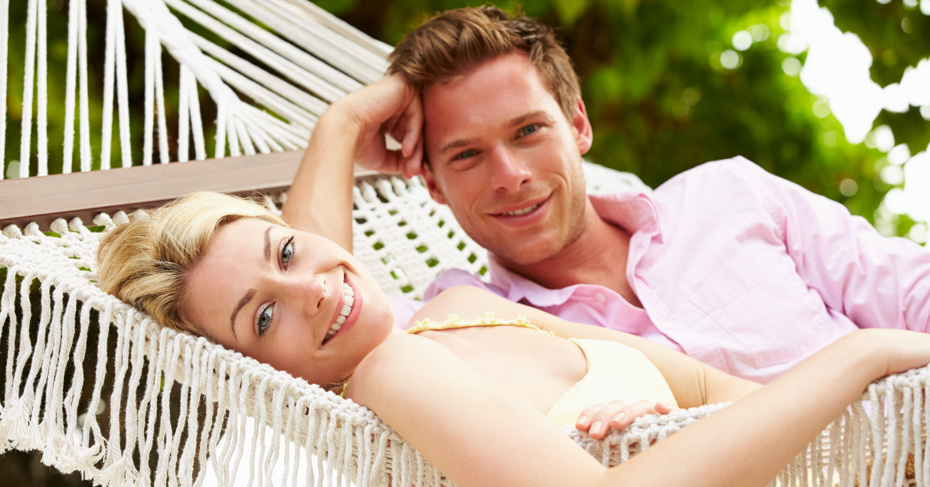 Bimini Bahamas cruise with Couple Relaxing In Beach Hammock. Take a one day cruise to Bimini by plane with Bahamas Air Tours