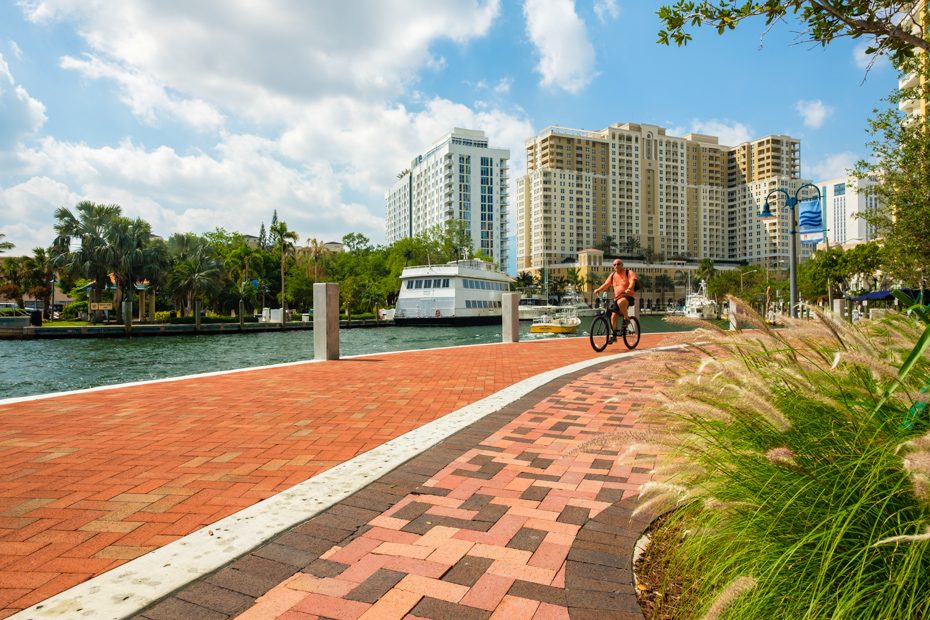 Fort Lauderdale, Florida - March 20, 2018: Cityscape view of the popular Las Olas Riverwalk downtown district with a visitor riding a bicycle along the promenade. For all the top things to do in Fort Lauderdale, or what to do in Fort Lauderdale that you haven't thought of yet, check out this comprehensive list of fun things to do in Fort Lauderdale and all Fort Lauderdale activities such us a day tour Bahamas from Bahamas Air Tours.