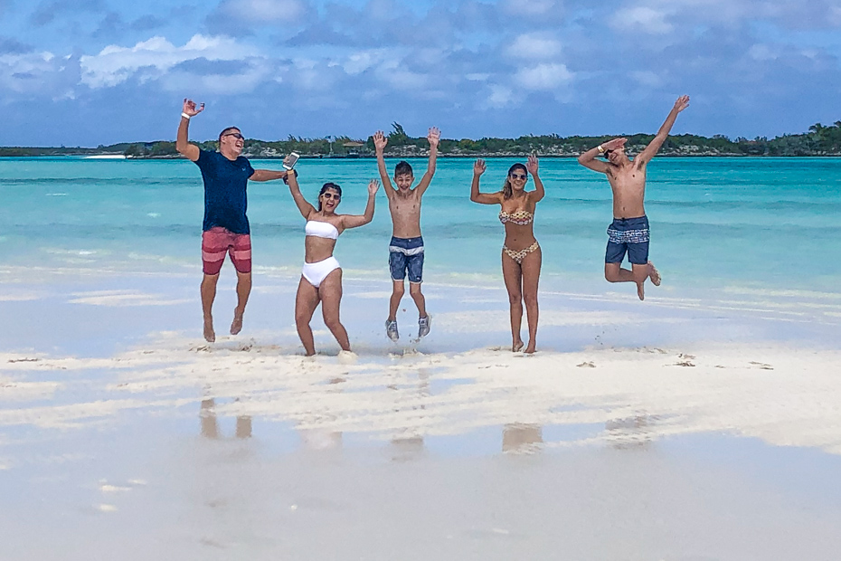 Family enjoying the Exuma Cays Sand Bar at Pipe Creek close to Staniel Cay Exuma Bahamas.