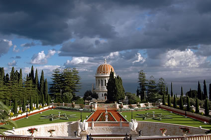 The completed Shrine of the Báb and gardens. The circle of cypress trees where Bahá'u'lláh stood can be seen on the right side of the Shrine.