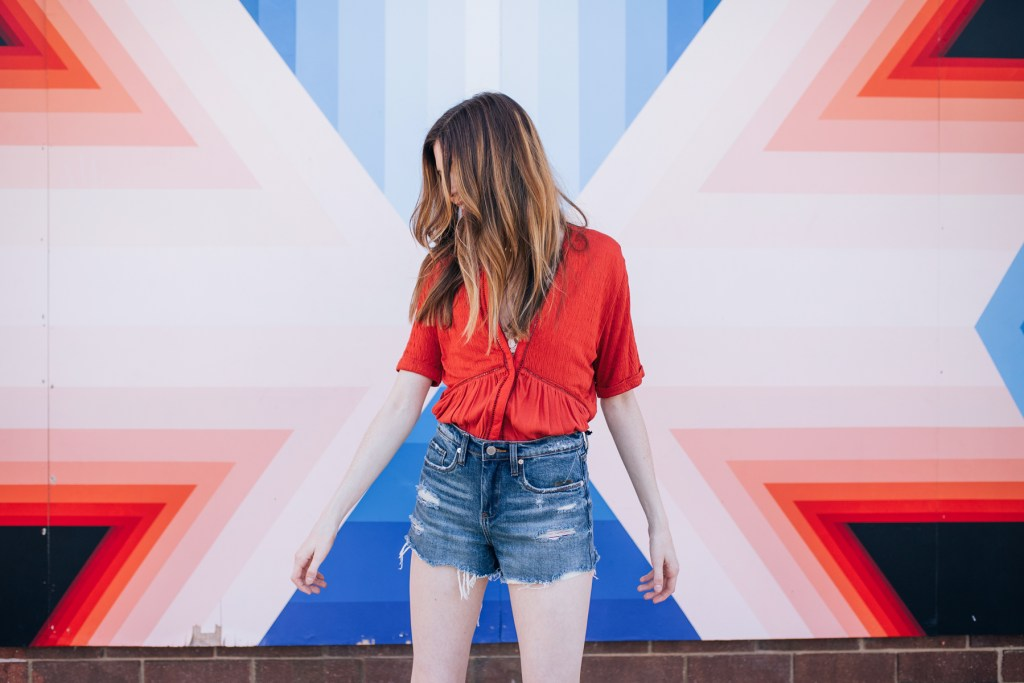 Bailey in front of a mural in Raleigh wearing Anthropologie as well as Free People and Blank NYC from South Moon Under