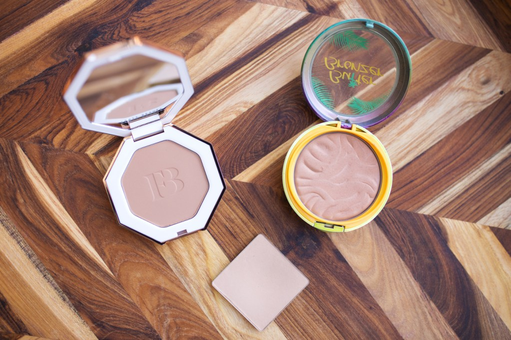 three light bronzers: physican's formula butter bronzer in 'light'. fenty beauty sun stalk'r bronzer in 'inda sun' and benefit hoola bronzer in 'lite'