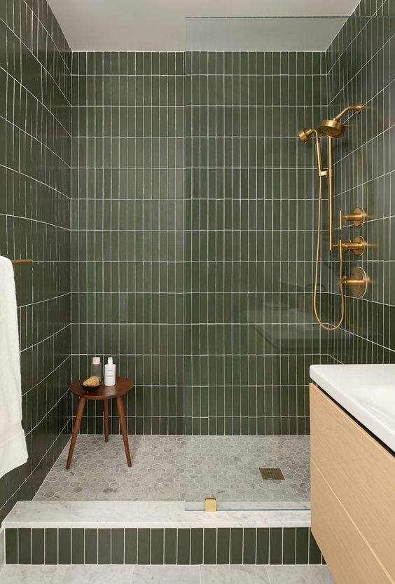 stacked earthy green subway tile shower with gold fixtures
